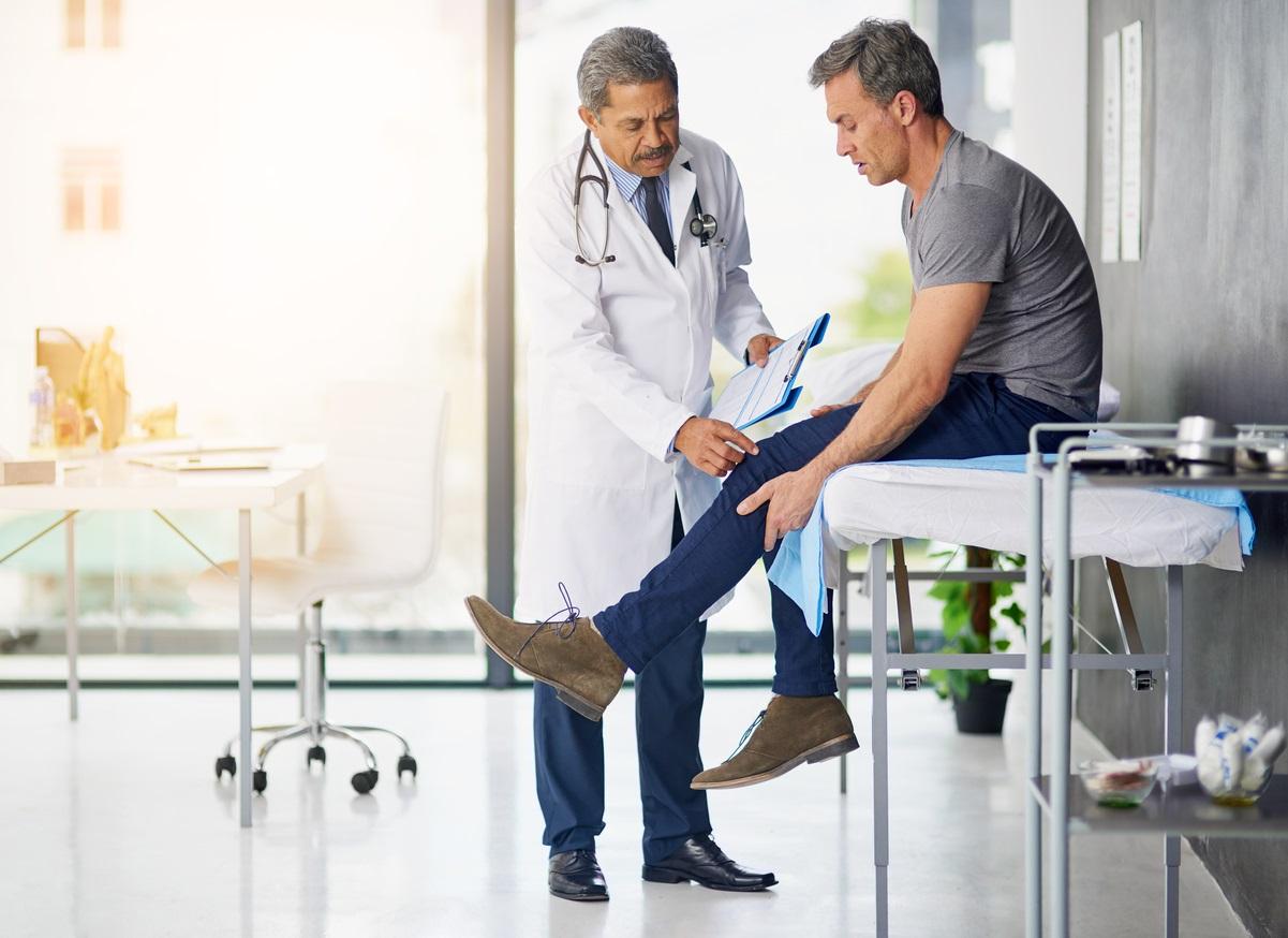 Médico avaliando pernas do paciente sentado na maca | Dores nas pernas
