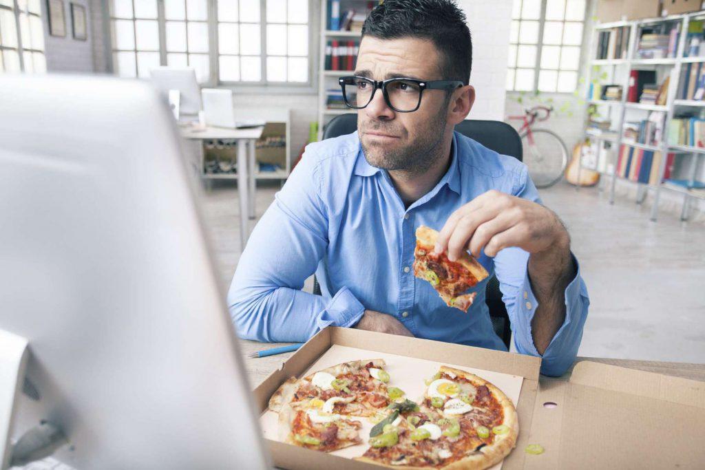 Homem comendo pizza em frente ao computador | O sedentarismo e a má alimentação podem causar doenças cardiovasculares