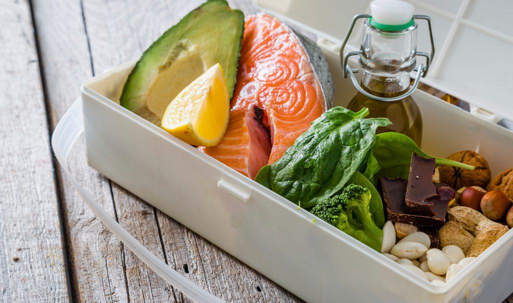 Caixa com alimentos saudáveis, como abacate, peixe e verduras | Alimentos que combatem as doenças cardiovasculares