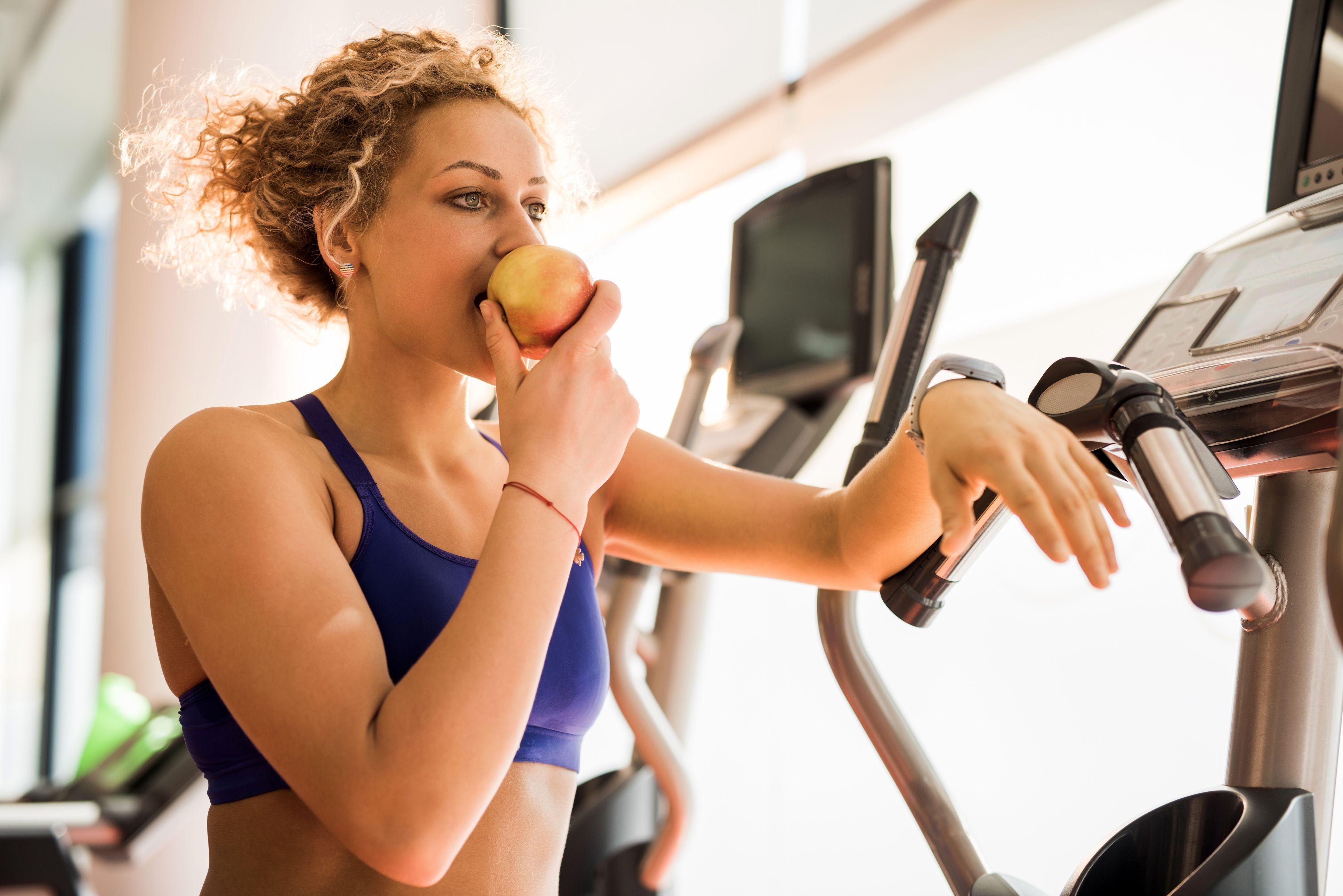 Mulher comendo maçã no intervalo do exercício físico | Prevenção de doenças cardiovasculares