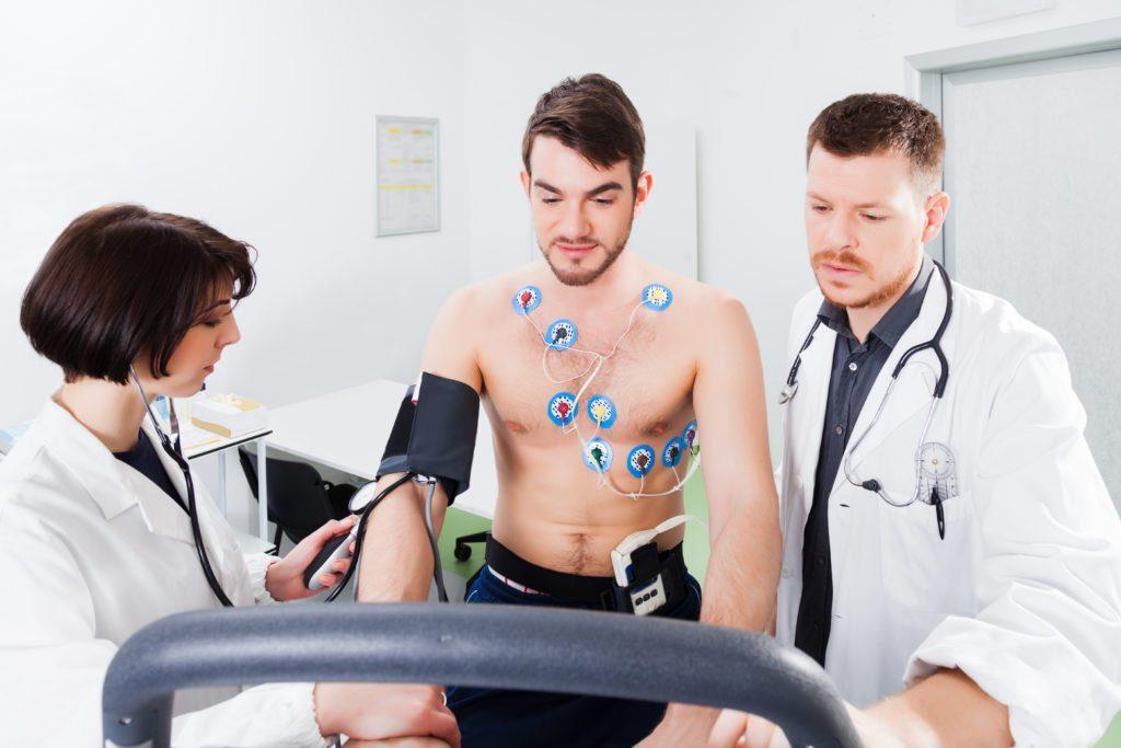 Paciente fazendo exame no coração e medindo pressão acompanhado de um médico e uma médica | Como identificar as doenças do coração?