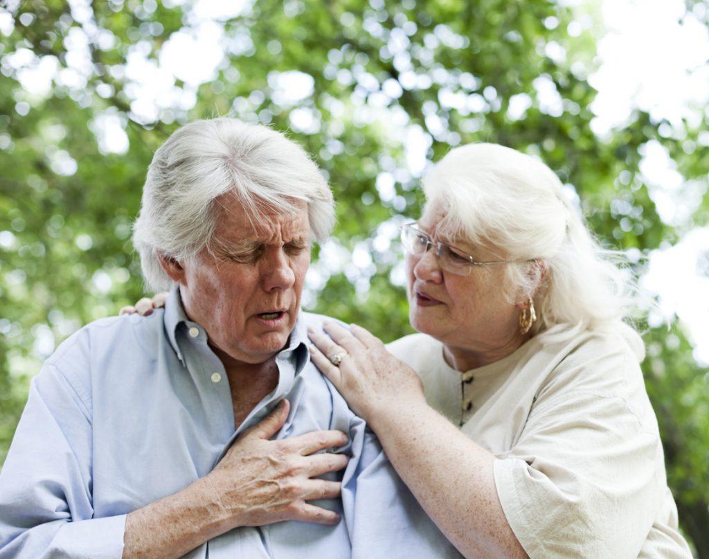 Idoso sentindo dor no peito e mulher o amparando | Infarto