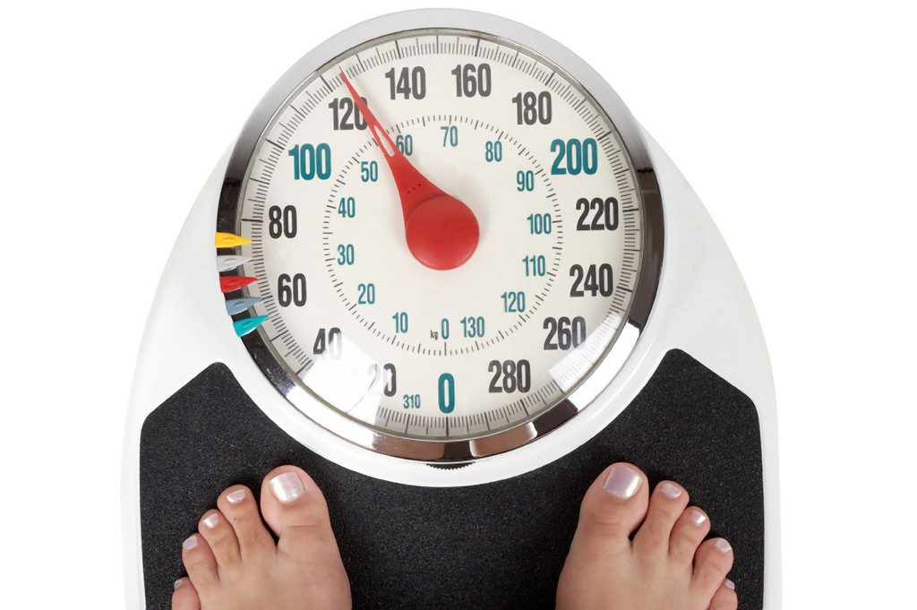 Balança com pessoa se pesando | Quais são os sintomas da diabetes?