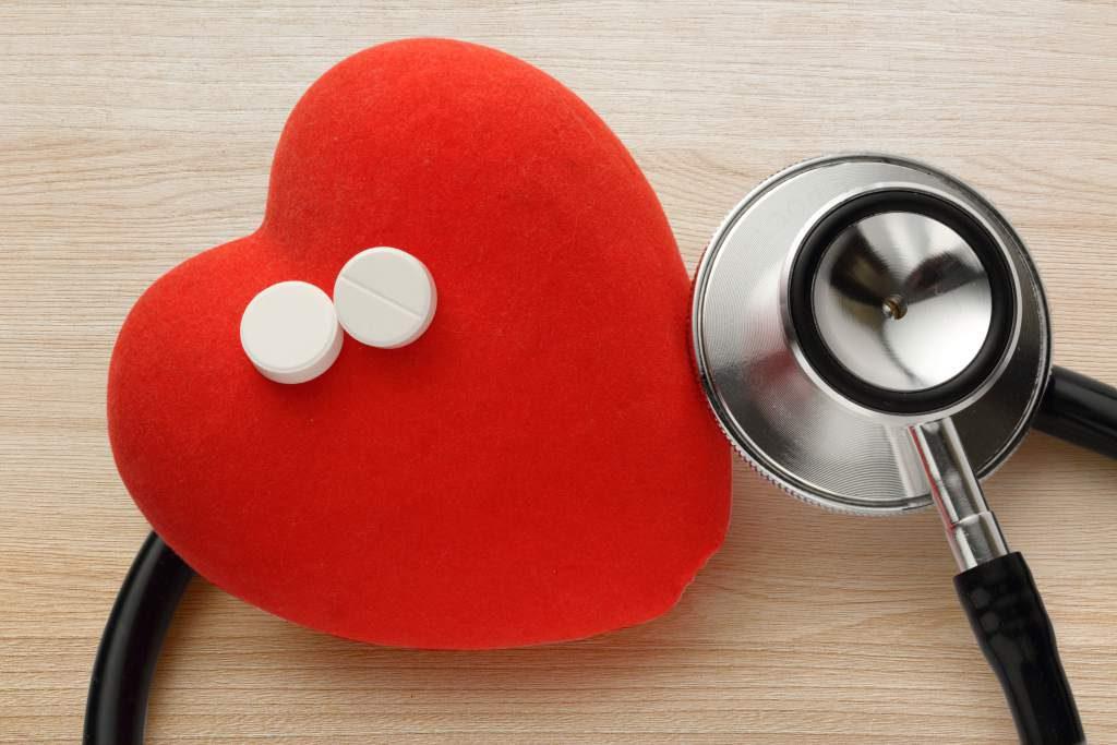 Coração de pelúcia com dois comprimidos em cima e um estetoscópio ao lado | Genéricos para tratar doenças cardiovasculares