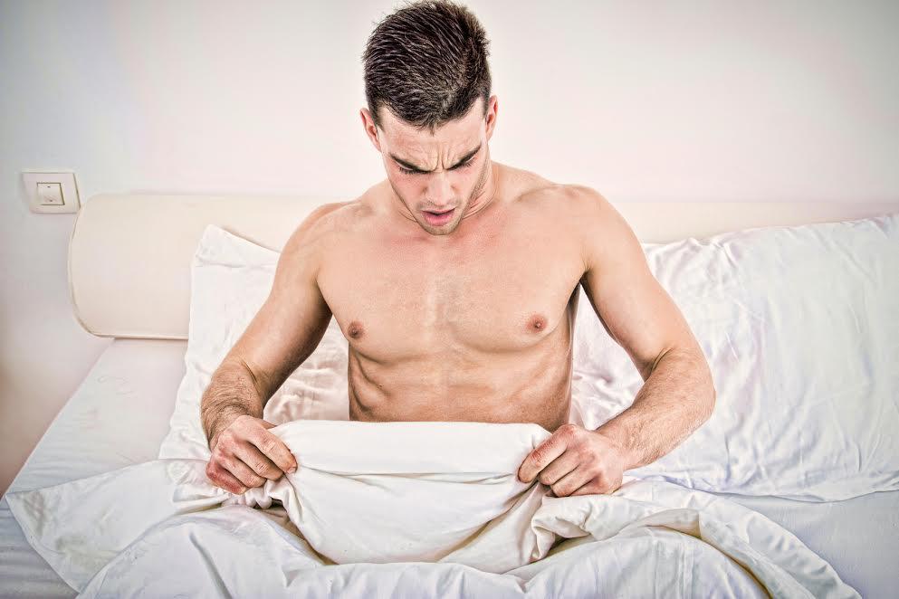 Homem olhando assustado para o pênis debaixo do lençol | O que é disfunção erétil?