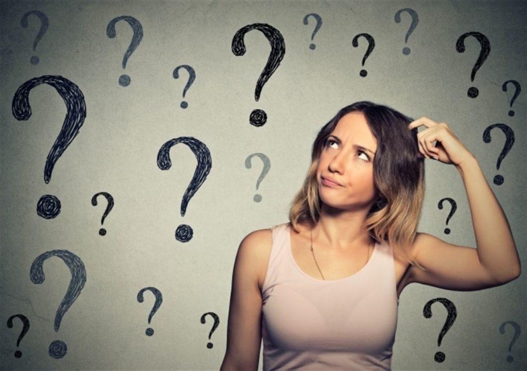 Mulher com cara de dúvida e vários pontos de interrogação | O que é a diabetes?