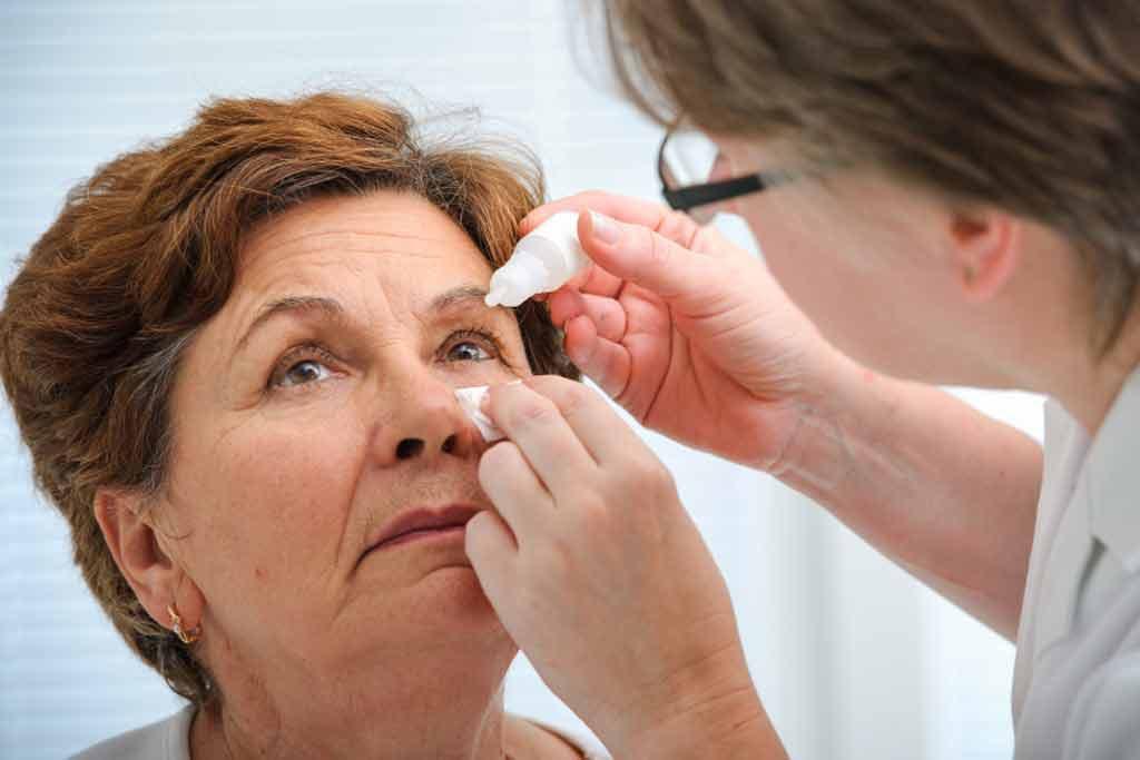 Mulher com glaucoma recebendo aplicação de colírio da médica | Possíveis complicações da diabetes