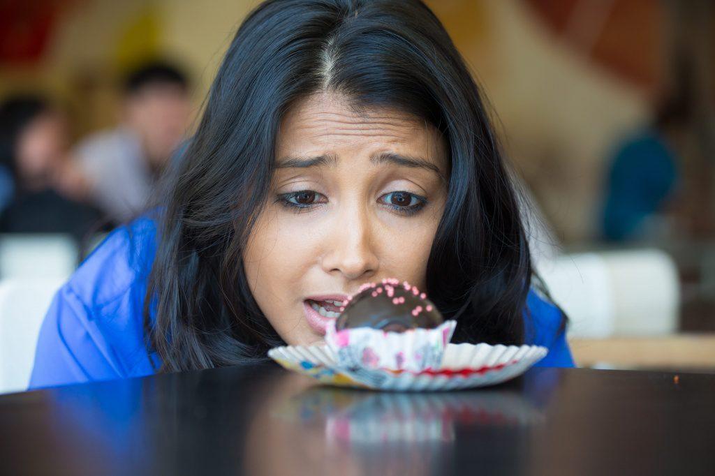 Mulher olhando fixamente o doce na mesa | Mitos e verdades sobre a diabetes