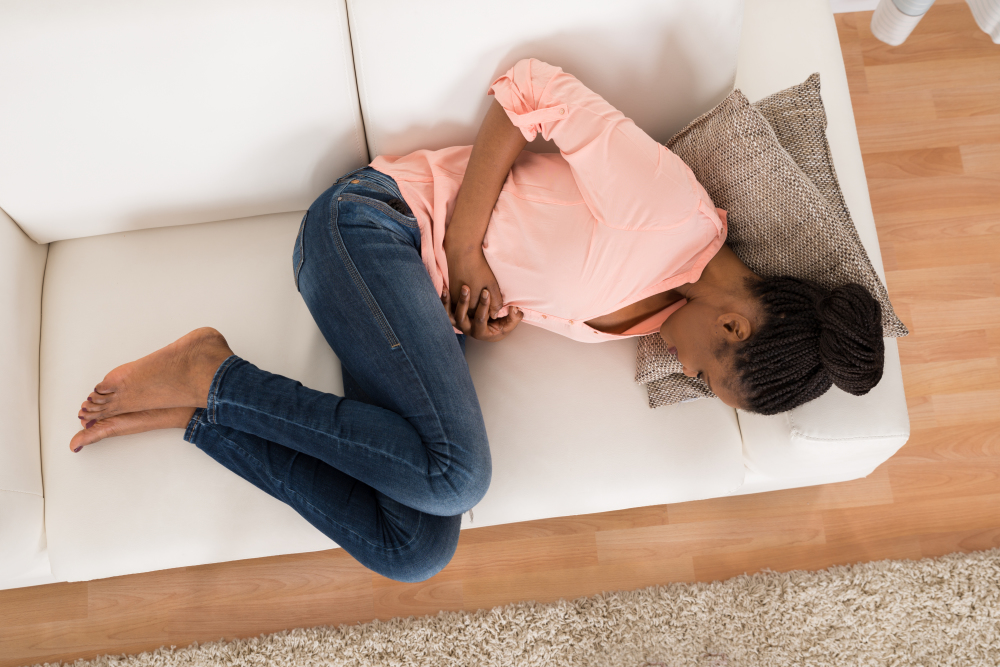 Mulher se sentindo mal no sofá | Quais são os sintomas da diabetes?