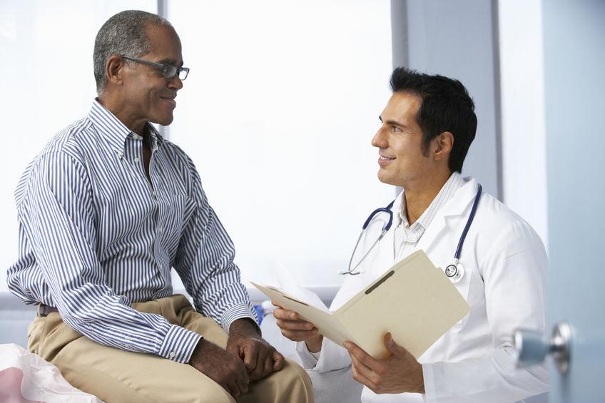 Senhor sentado na maca em frente ao médico que segura uma pasta | Tratamento da disfunção erétil