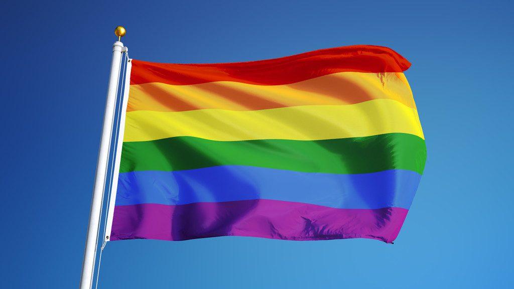 Bandeira colorida do movimento LGBT balançando num mastro   Estereótipo do portador do vírus HIV
