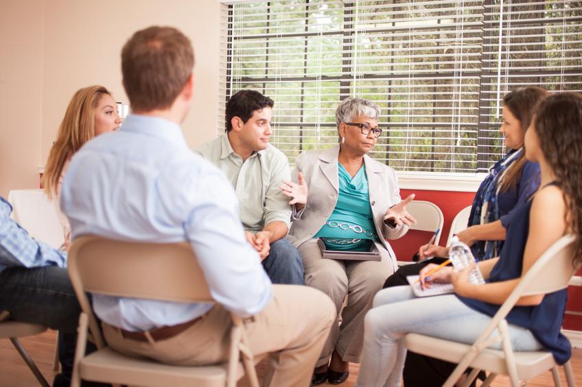 Grupo de sete pessoas sentadas em círculo e conversando | Apoio e direitos do portador do HIV