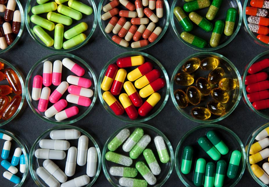 Vários potes com cápsulas de remédios em diferentes cores | Remédios e tratamentos para controlar o vírus do HIV
