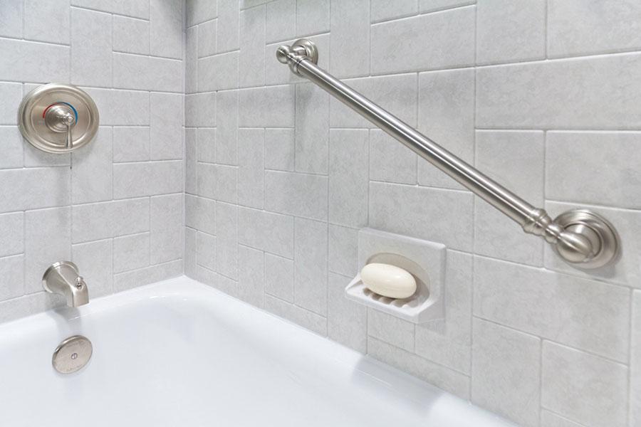 Banheiro com barra de apoio feita de ferro na parede para evitar quedas | Adapte sua casa