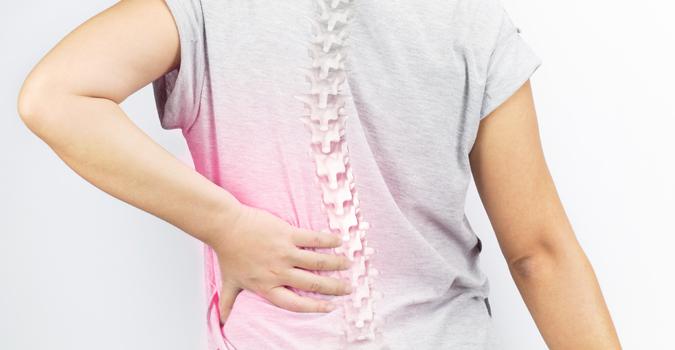 Mulher com a mão nas costas em sinal de cor | Causas da osteoporose
