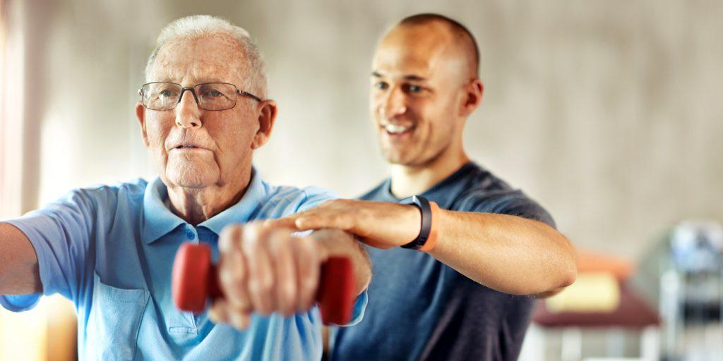 Idoso faz exercícios com haltere junto com instrutor | Tratamento da osteoporose