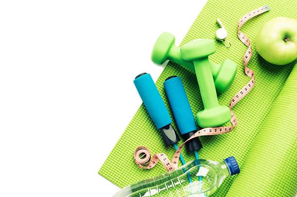 Imagem composta por halteres, fita métrica, garrafa de água e maçã verde | Prevenção da queda de cabelo