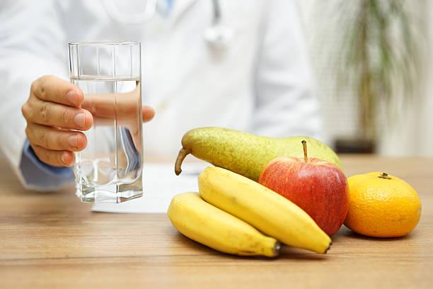 Médico segurando uma copo de água e a sua frente diversas na mesa | Alimentos que ajudam a combater a enxaqueca