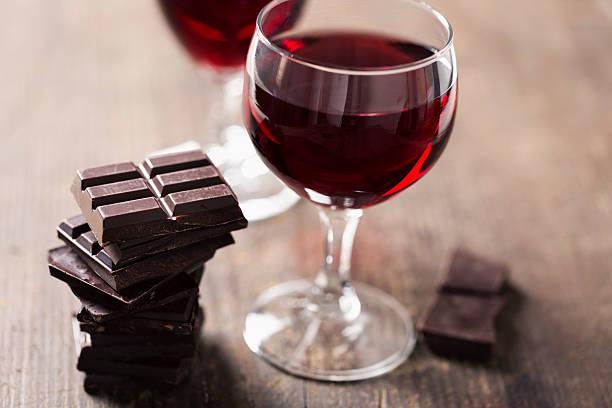 Barras de chocolate uma taça com vinho em cima de uma mesa | Alimentos perigosos para a enxaqueca