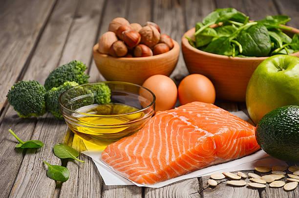 Mesa com azeite, salmão, ovos, maçã verde e brócolis | Alimentos benéficos para a saúde do cabelo