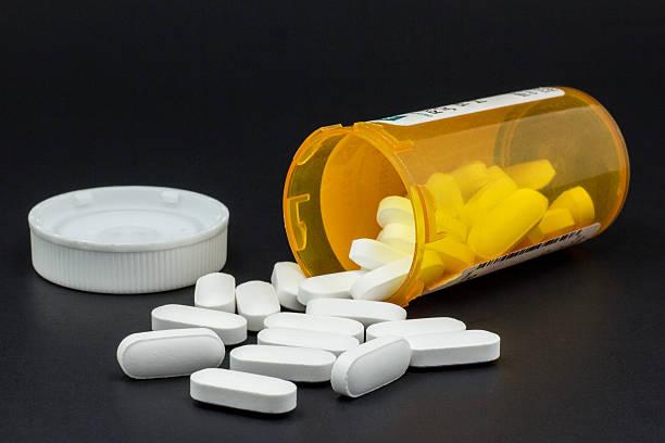 Pote de medicamento caído em cima da mesa com pilulas para fora | Uso de analgésicos durante as crises de enxaquecas