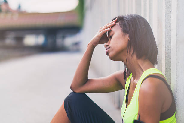 Mulher com roupa de ginástica sentada na rua com uma das mão na cabeça | Causas da enxaqueca