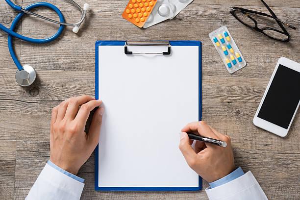 Médico escreve em sua prancheta que está e cima da mesa junto com celular, óculos, medicamento e estetoscópios | Diagnóstico da enxaqueca
