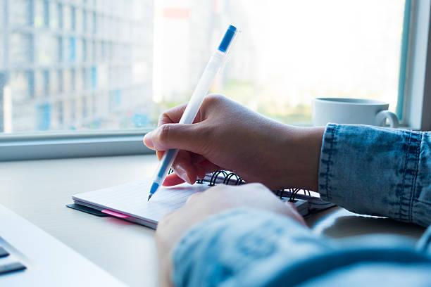 Pessoa escrevendo em um caderno | Anote num caderno as crises de enxaqueca
