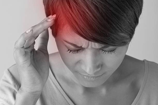 Mulher com uma das mãos na cabela |Diferença entre enxaqueca e dor de cabeça