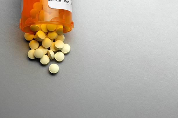 Pílulas caídas do potinho de medicamento em cima de uma superfície cinza | Medicamento para queda de cabelo