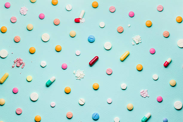 Vários e diferentes comprimidos em cima de uma superfície azul | Medicamentos para endometriose