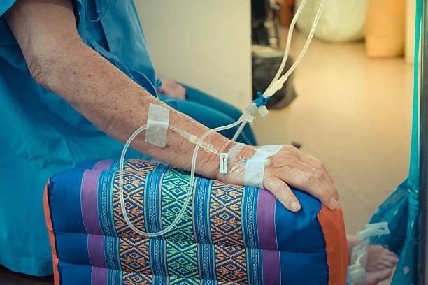 Mulher sentada recebendo medicamento direto na veia da mão | Queda de cabelo durante a quimioterapia