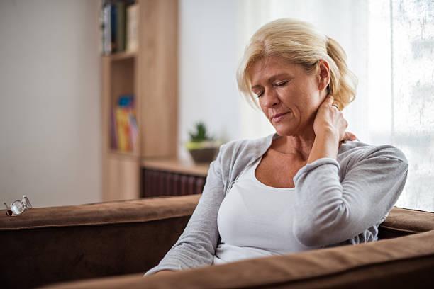 Mulher sentada numa poltrona e com uma das mãos no pescoço | Sintomas da endometriose