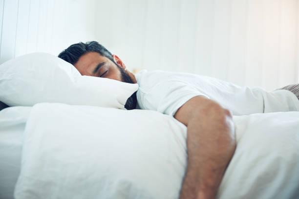 Homem dormindo em uma cama | Tratamento da enxaqueca