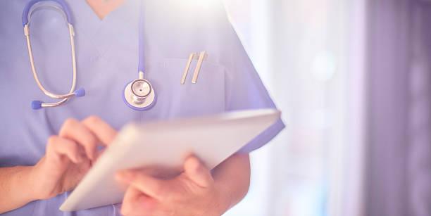Médico com um tablet nas mãos fazendo anotações | Tratamento da queda de cabelo