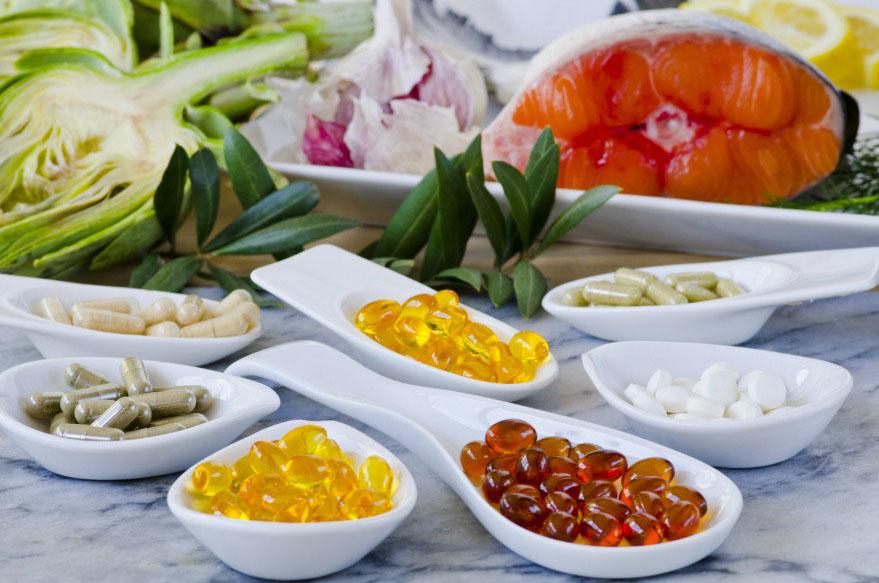Cápsulas de vitaminas em potes brancos em volta de legumes e verduras